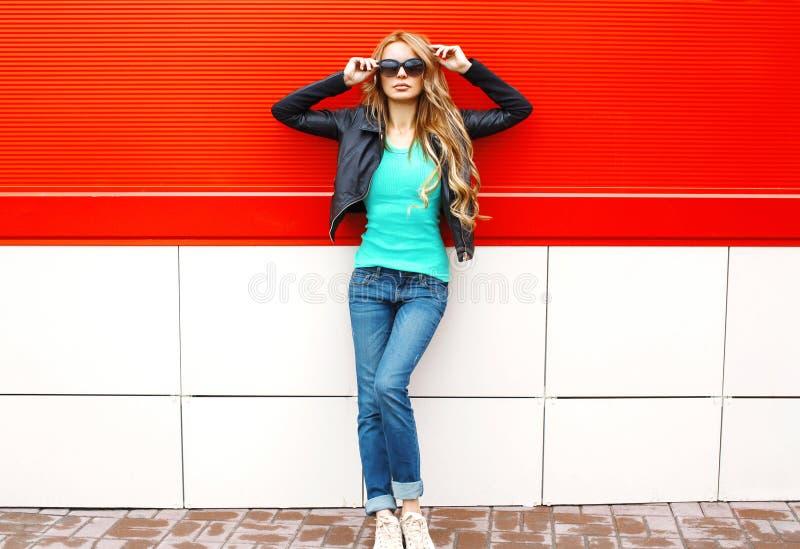 塑造在摆在红色的城市的太阳镜黑岩石夹克的俏丽的妇女模型 免版税库存照片