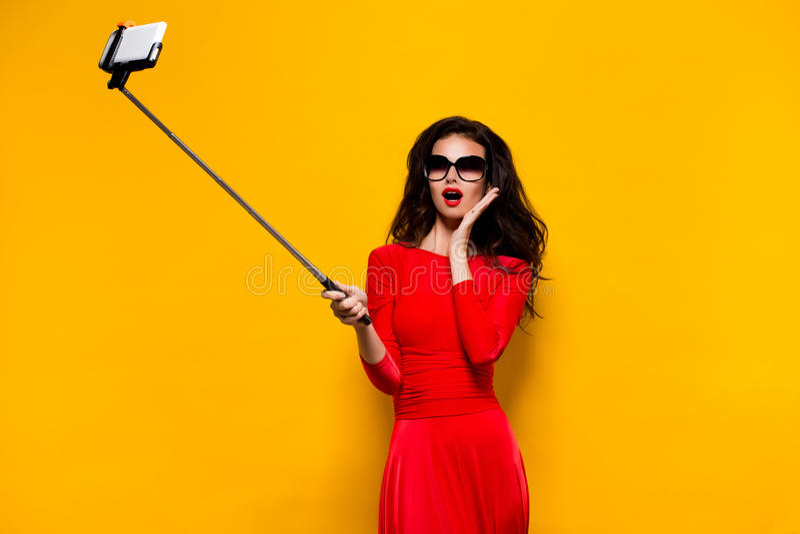 塑造在有采取selfie的开放嘴的红色礼服 库存照片