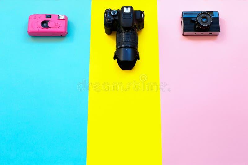 塑造在黄色,蓝色和桃红色背景的三台照相机 热的夏天震动 流行艺术 晴朗的夏天静物画 明亮的甜fashio 免版税库存图片