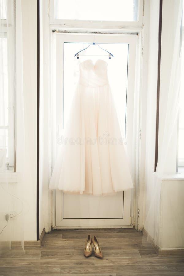塑造垂悬在窗口附近的新娘的婚礼礼服 免版税图库摄影