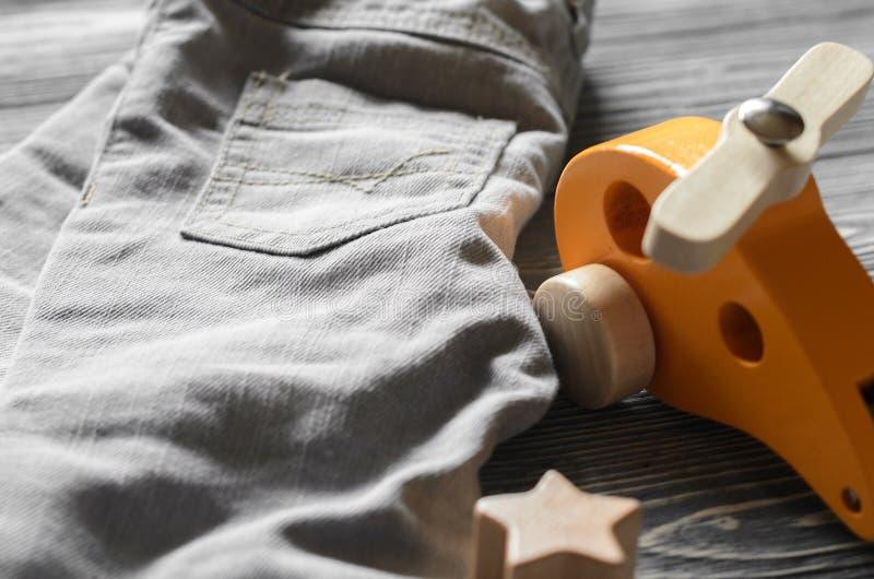 塑造孩子牛仔布裤子和黄色玩具直升机 婴孩衣物 免版税库存照片