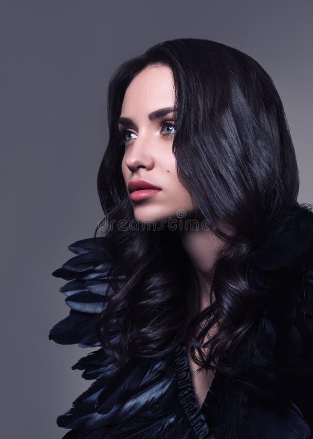 塑造年轻美丽的妇女画象黑色的 黑发和黑羽毛 库存照片