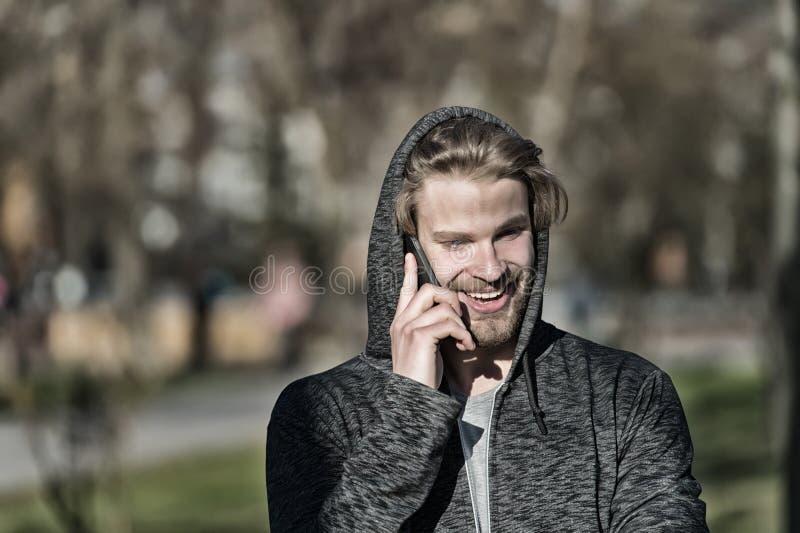 塑造强壮男子微笑与在偶然运动衫的智能手机 敞篷谈话的愉快的人在晴朗室外的手机 有胡子的人s 免版税库存图片