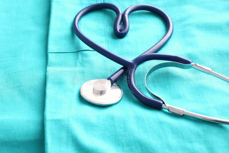 塑造心脏和剪贴板在医疗制服,特写镜头的听诊器 免版税库存图片