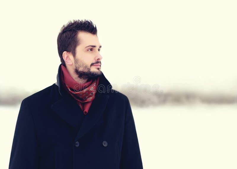 塑造户外穿在迷离背景的英俊的有胡子的深色的人画象黑外套 库存照片