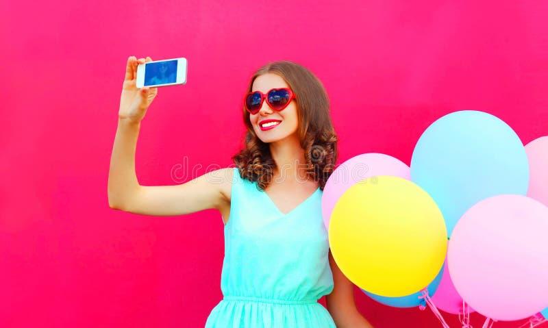 塑造拍在一个智能手机的微笑的妇女一张照片有在桃红色背景的空气五颜六色的气球的 库存照片