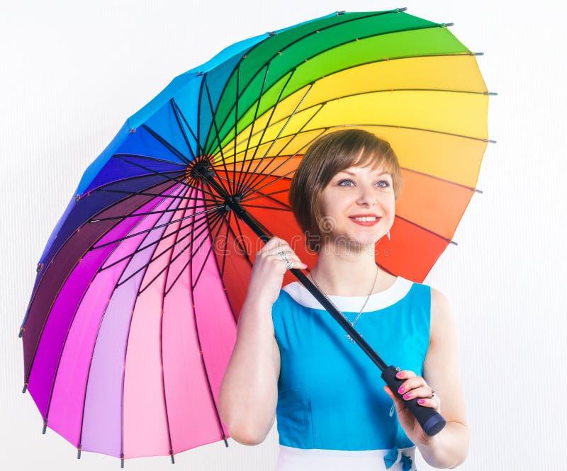 塑造拿着五颜六色的彩虹伞的相当微笑的少妇穿在白色背景的一件蓝色礼服 演播室射击,拷贝 库存照片