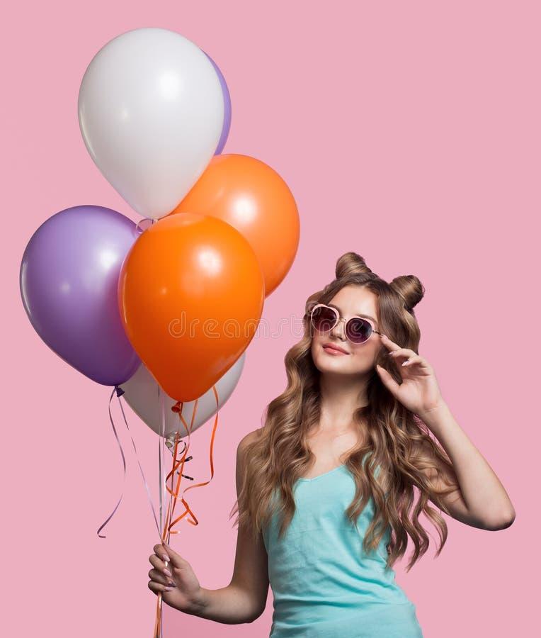 塑造拿着在桃红色背景的妇女桃红色气球 免版税库存图片