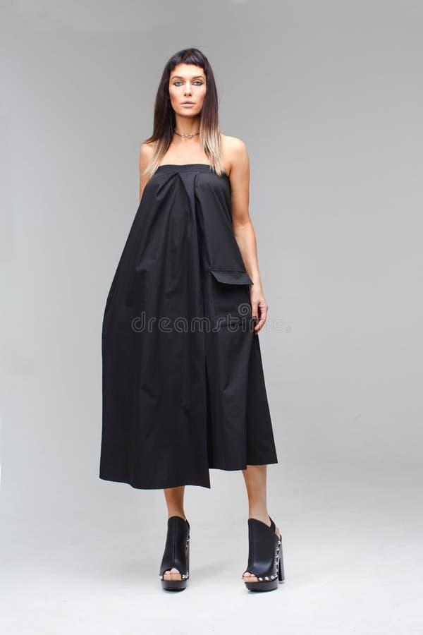 塑造拿着礼服手中黑sundress 免版税库存照片