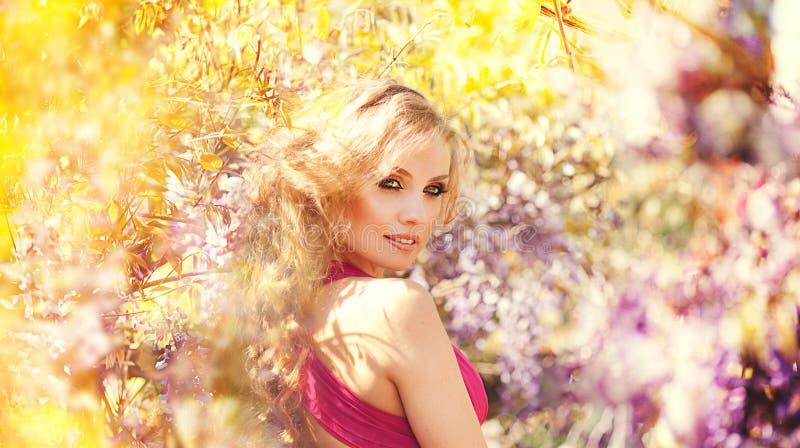 塑造摆在反对在开花的淡紫色灌木的年轻美丽的女孩画象  图库摄影
