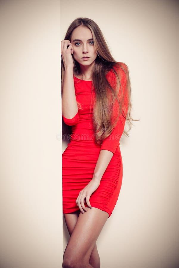 塑造摆在墙壁附近的红色礼服的妇女 库存图片