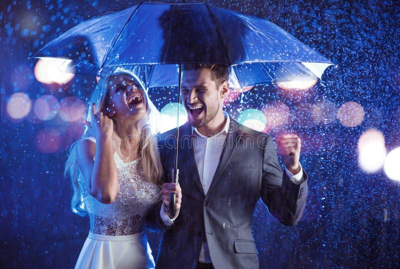 塑造摆在多雨天气的夫妇的样式画象 库存图片