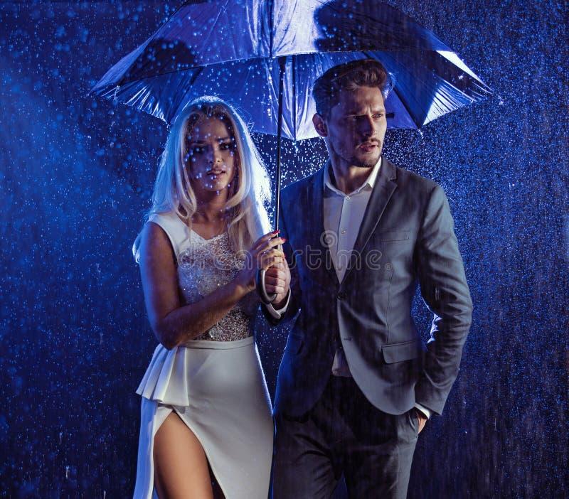 塑造摆在多雨天气的夫妇的样式画象 免版税库存图片