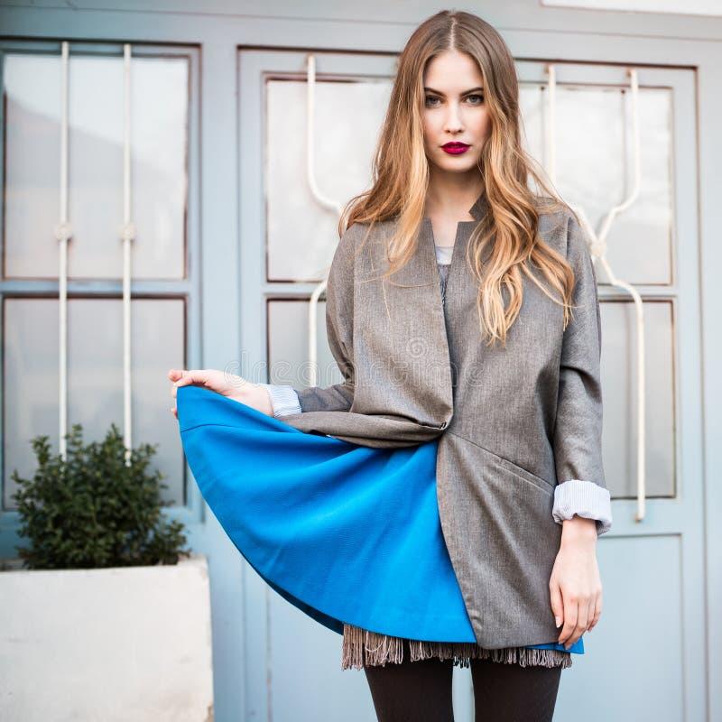 塑造摆在房子附近的夹克和蓝色礼服的夫人 免版税库存照片
