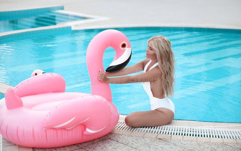 塑造摆在桃红色的白色比基尼泳装的性感的白肤金发的式样妇女  免版税库存图片
