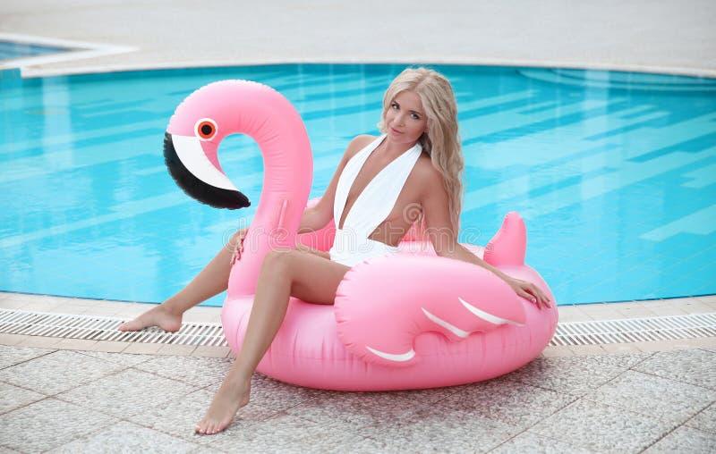 塑造摆在桃红色的白色比基尼泳装的性感的白肤金发的式样妇女  免版税库存照片