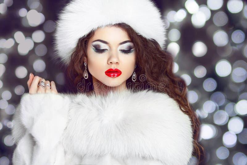 塑造摆在皮大衣和白色毛茸的帽子的女孩模型 Winte 图库摄影