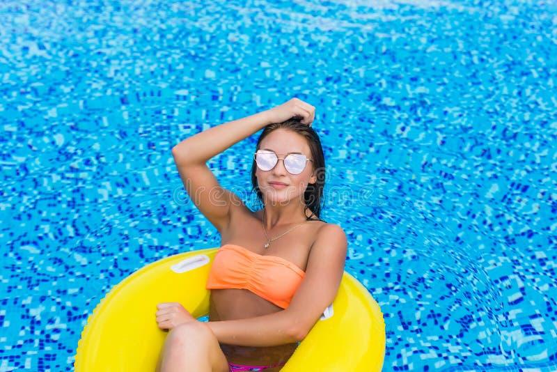 塑造放松漂浮在可膨胀的圆环的性感的美丽的女孩和太阳镜照片黄色上面的 户外生活方式portrai 免版税图库摄影