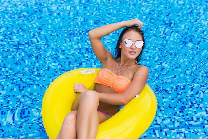 塑造放松漂浮在可膨胀的圆环的性感的美丽的女孩和太阳镜照片黄色上面的 户外生活方式portrai 库存图片
