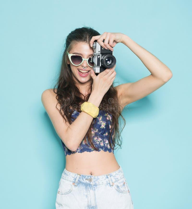 塑造时髦的妇女跳舞和制造照片使用减速火箭的照相机 在蓝色背景的画象在白色毛线衣 库存图片