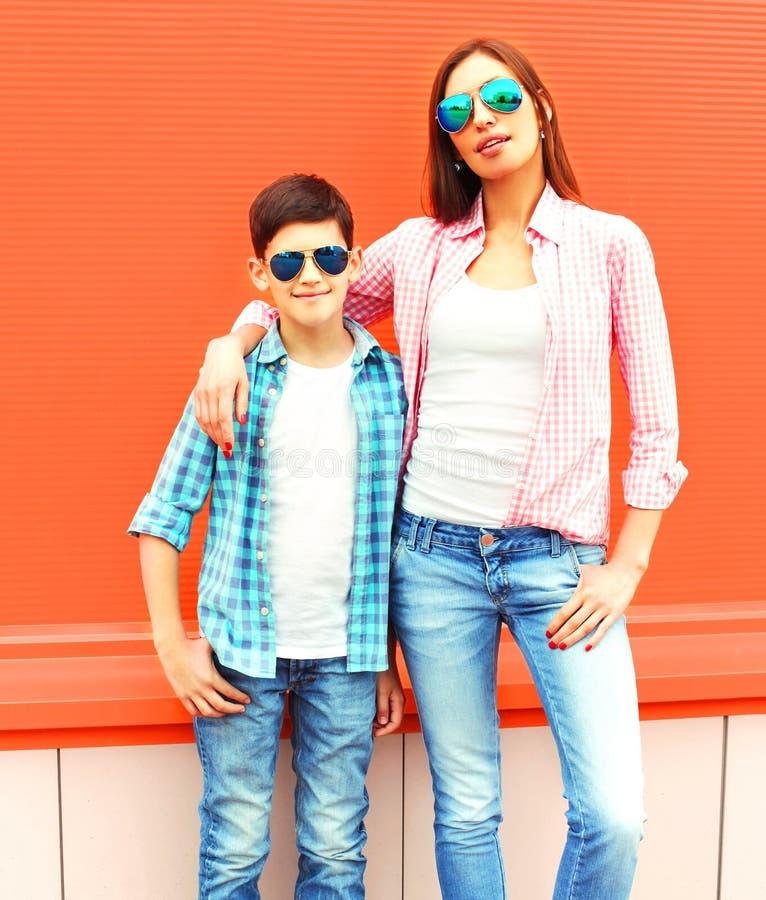 塑造有儿子少年的母亲的太阳镜,方格的衬衣 免版税库存图片