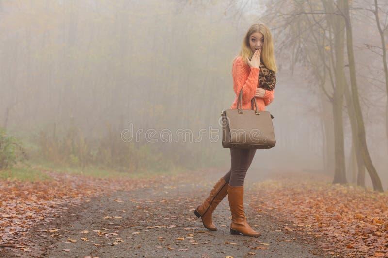 塑造有摆在秋天公园的提包的妇女 免版税图库摄影