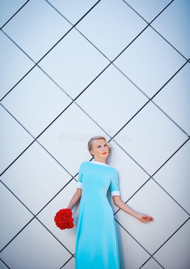 塑造有明亮性感的白肤金发的妇女组成相当年轻行家,白色都市墙壁背景的演播室画象  图库摄影