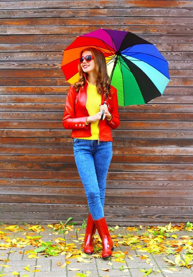 塑造有穿一双红色皮夹克和胶靴在木背景的秋天的五颜六色的伞的俏丽的妇女 免版税库存照片