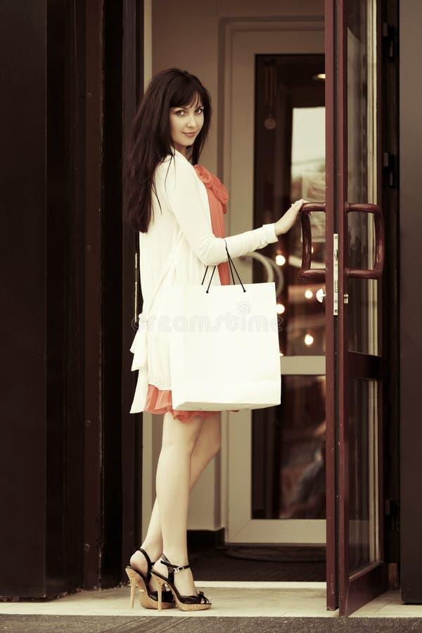 塑造有购物袋的妇女在购物中心门道入口 免版税库存图片