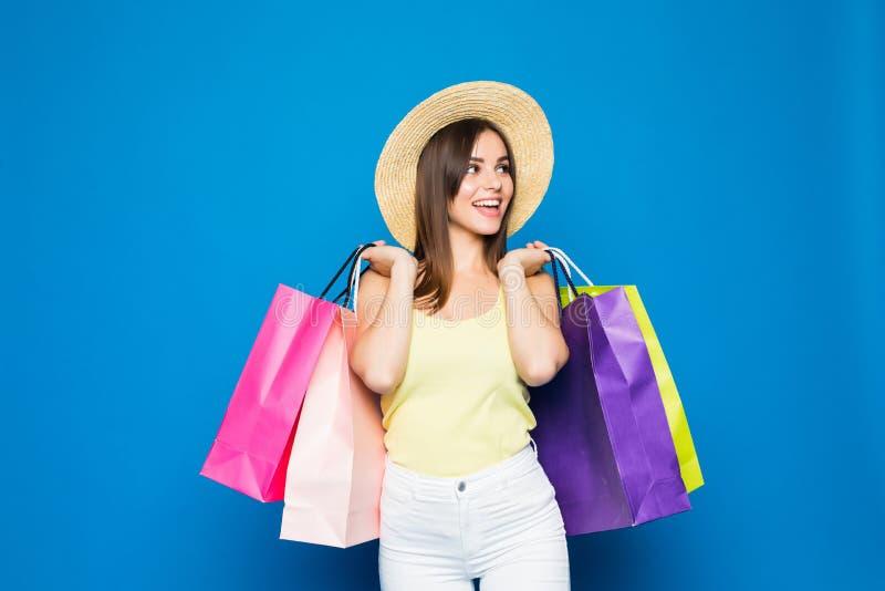 塑造画象年轻微笑的妇女佩带的购物袋,在五颜六色的蓝色背景的草帽 免版税库存照片