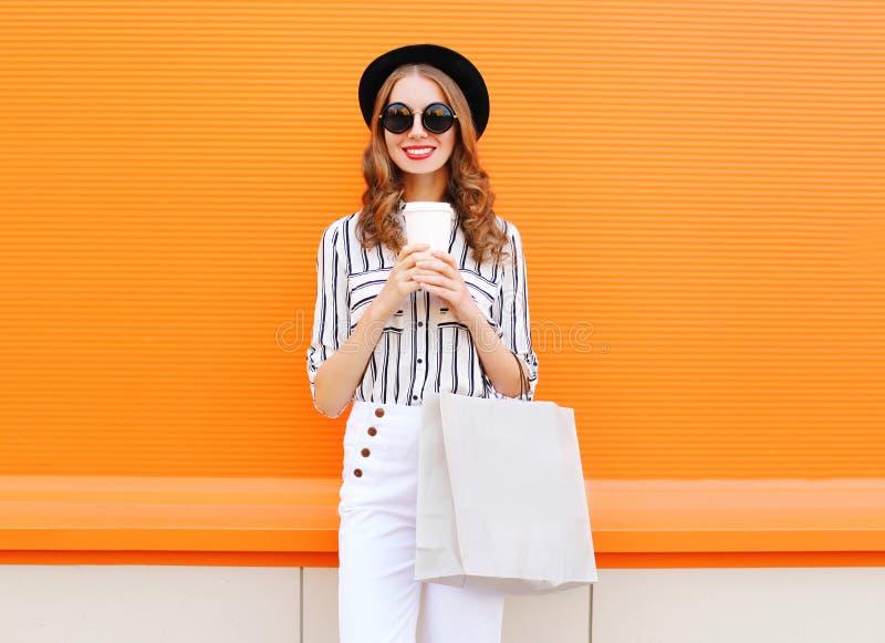 塑造相当与拿着咖啡杯的购物袋的年轻微笑的妇女模型穿在五颜六色的桔子的黑帽会议白色裤子 免版税图库摄影