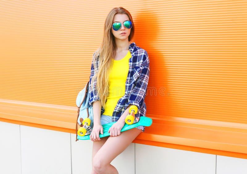 塑造相当凉快女孩佩带有滑板的太阳镜在五颜六色 免版税库存照片