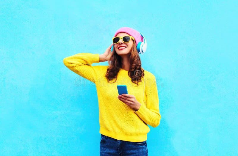 塑造相当听到在耳机的音乐的甜无忧无虑的妇女有戴五颜六色的桃红色帽子黄色太阳镜的智能手机的 免版税库存图片