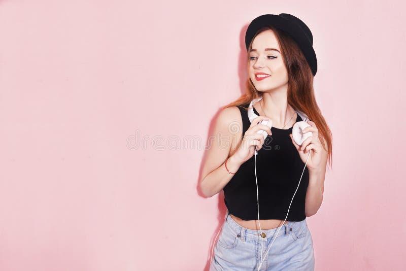 塑造相当帽子和耳机的凉快的妇女听到在桃红色背景的音乐的 帽子的美丽的年轻十几岁的女孩 库存图片