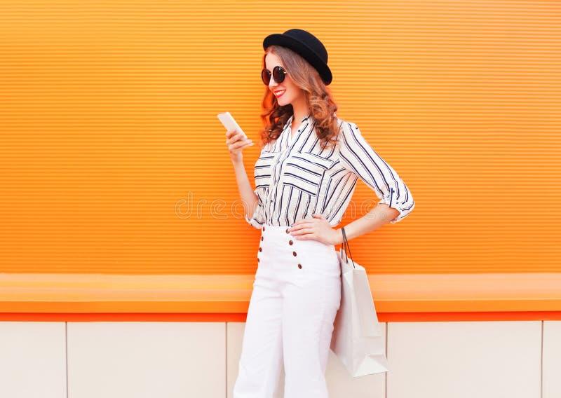 塑造相当愉快的年轻微笑的妇女模型使用有穿在五颜六色的购物袋的智能手机黑帽会议白色裤子 库存图片