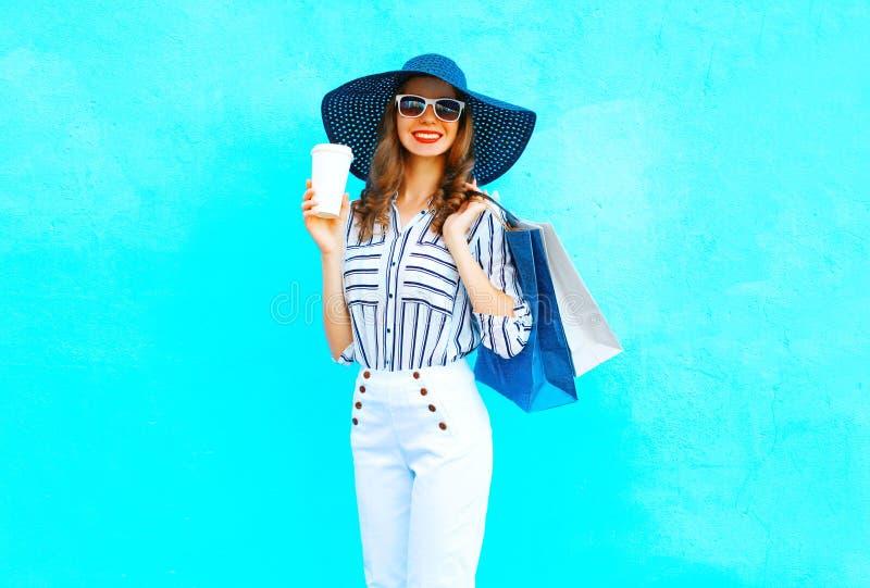 塑造相当有咖啡杯的年轻微笑的妇女佩带的购物袋,草帽,在五颜六色的蓝色背景的白色裤子 免版税库存图片