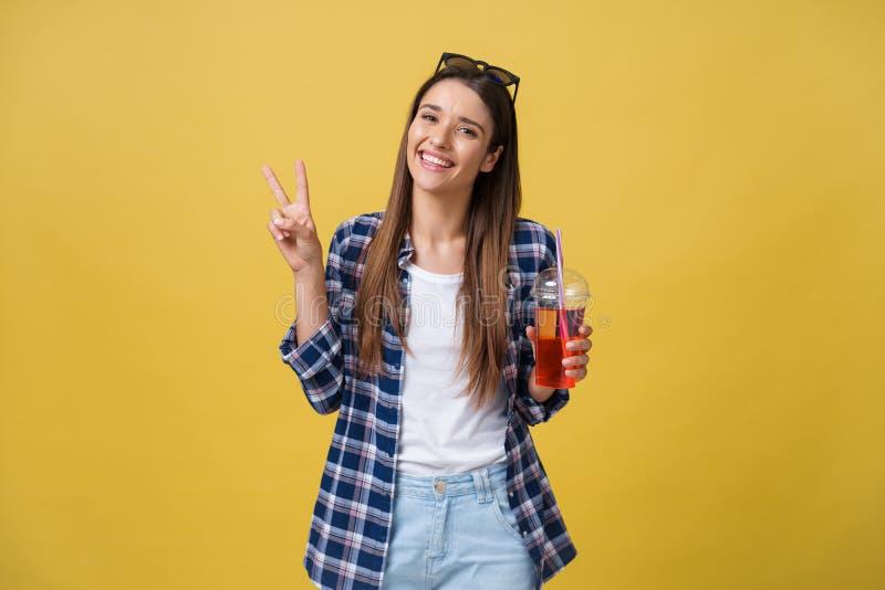 塑造相当有新鲜水果汁杯子的少妇在获得蓝色的衬衣在五颜六色的黄色背景的乐趣 免版税库存图片