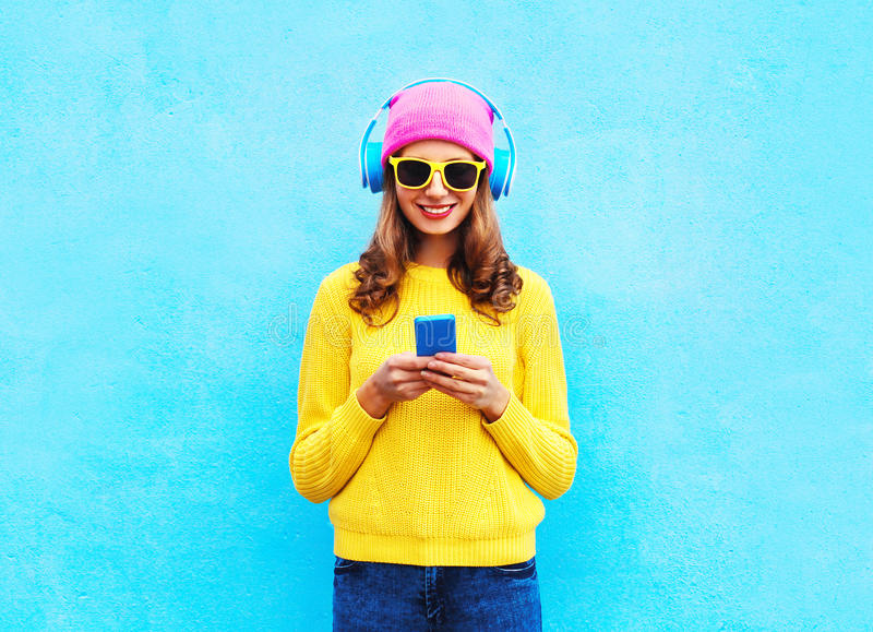 塑造相当甜无忧无虑的在浏览智能手机的耳机的妇女听的音乐戴五颜六色的桃红色帽子黄色太阳镜 图库摄影