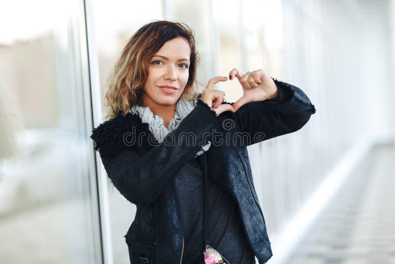 塑造相当皮夹克的甜少妇妇女,摆在被反映的窗口前面的黑牛仔裤 做心脏手, Fe 免版税库存照片