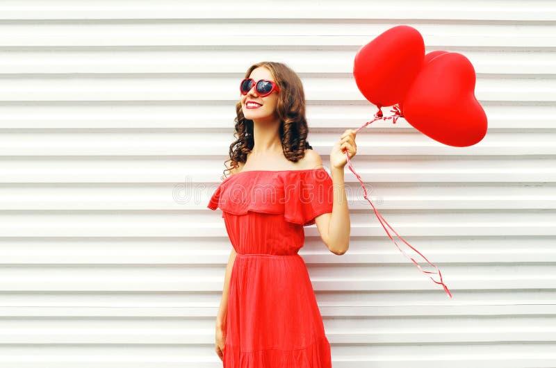 塑造相当红色礼服和太阳镜的愉快的微笑的妇女有气球查寻在白色的心脏形状的 免版税库存图片