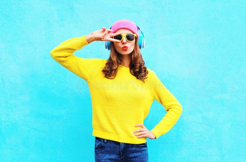 塑造相当耳机的凉快的女孩听到音乐的佩带的五颜六色的桃红色帽子黄色太阳镜和毛线衣在蓝色 图库摄影