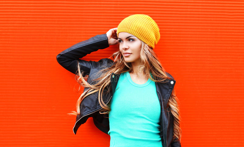 塑造相当年轻白肤金发的看在五颜六色的红色的外形的妇女佩带的夹克帽子 图库摄影