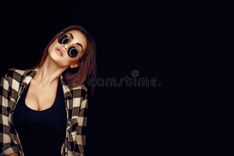 塑造秀丽女孩佩带的太阳镜,格子花呢上衣 免版税库存图片