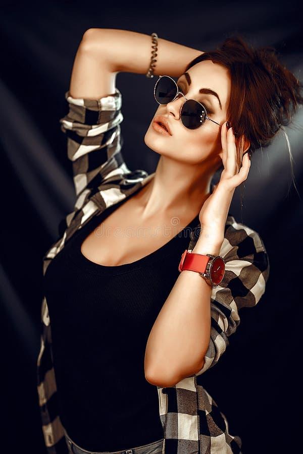 塑造秀丽女孩佩带的太阳镜,格子花呢上衣 库存图片