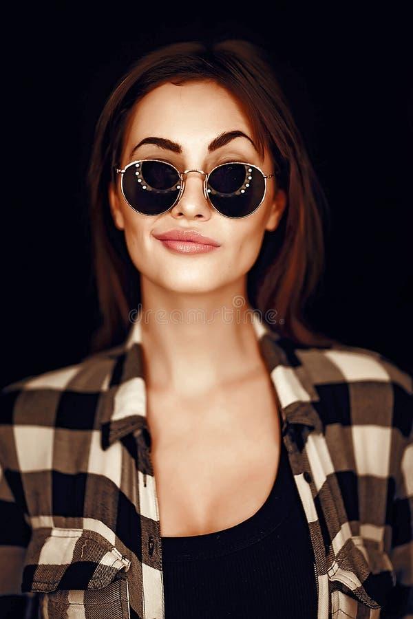 塑造秀丽女孩佩带的太阳镜,格子花呢上衣 库存照片