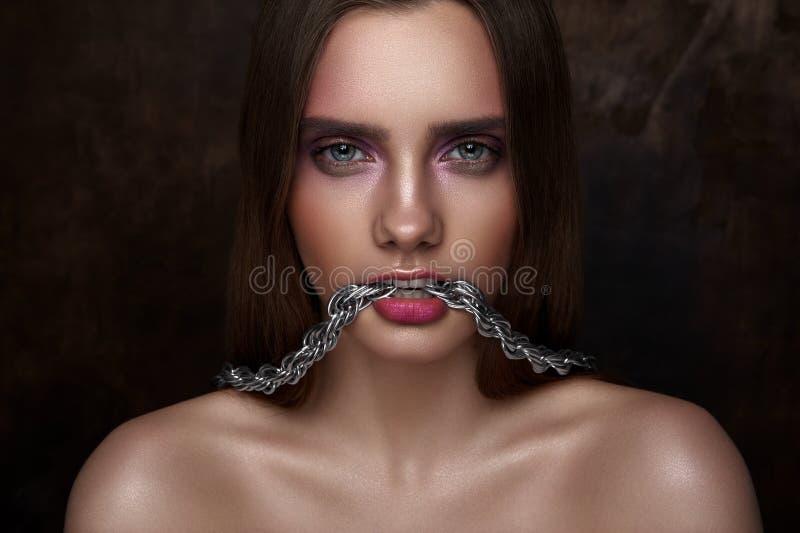 塑造秀丽有链子的少妇在她的牙 图库摄影