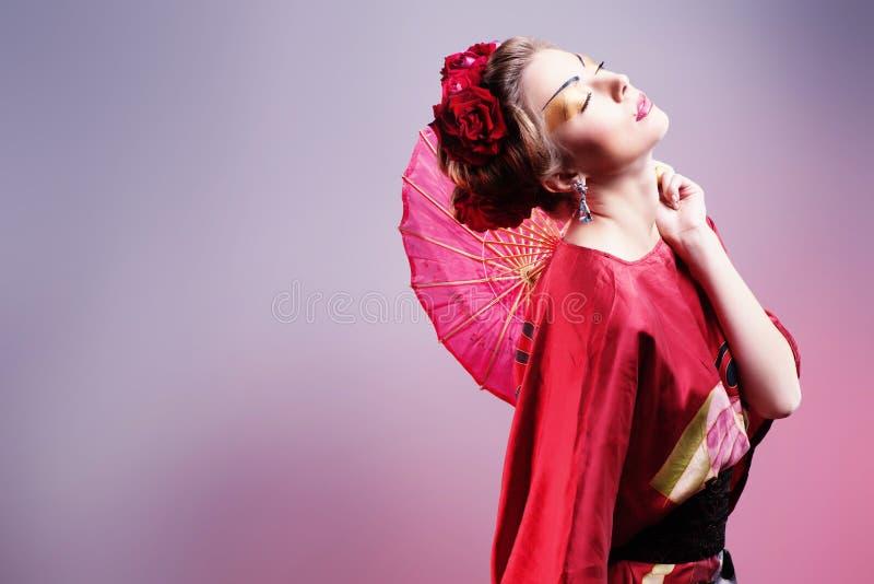 塑造穿传统日本红色和服的亚裔妇女。Gei 库存照片