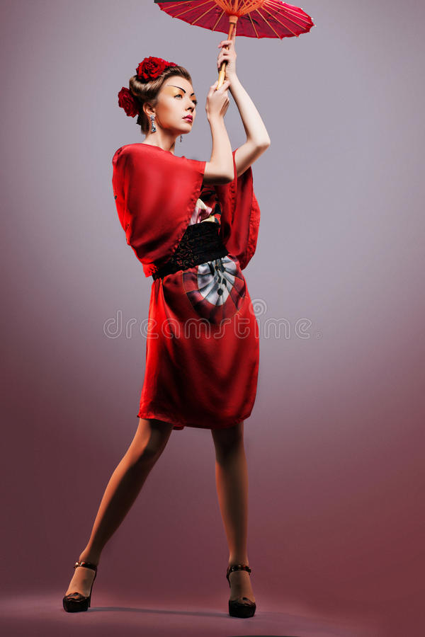 塑造穿传统日本红色和服的亚裔妇女 免版税图库摄影