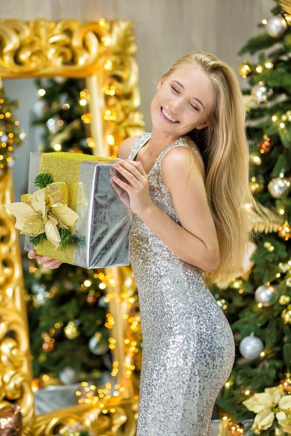 塑造美丽的华美的妇女夫人内部照片有金发的在摆在有圣诞树的屋子里的豪华礼服和 库存图片