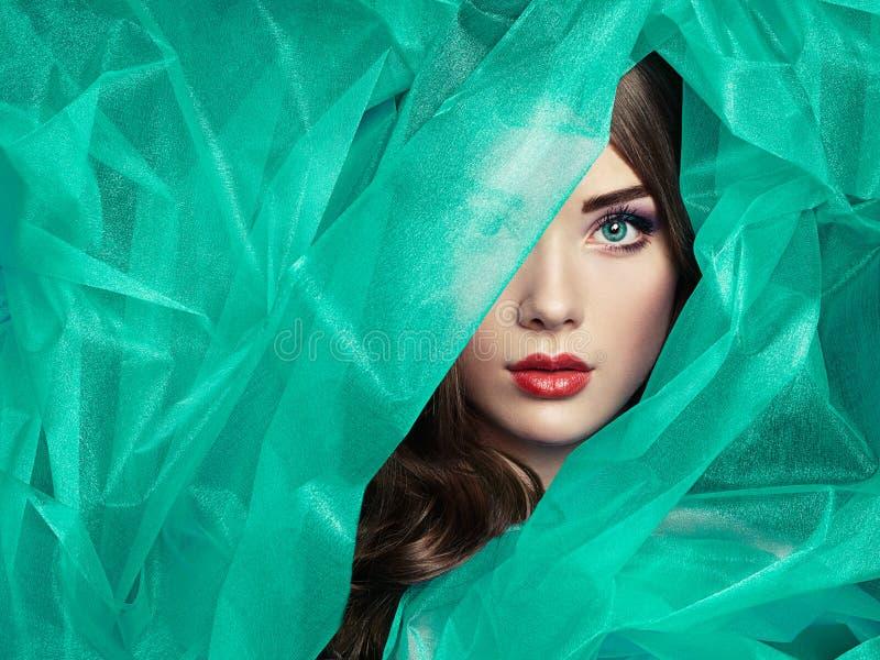 塑造美丽的妇女照片在绿松石面纱下 库存图片